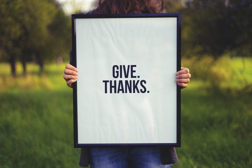 Frau hält Schild in die Luft auf dem Geben und Danke steht