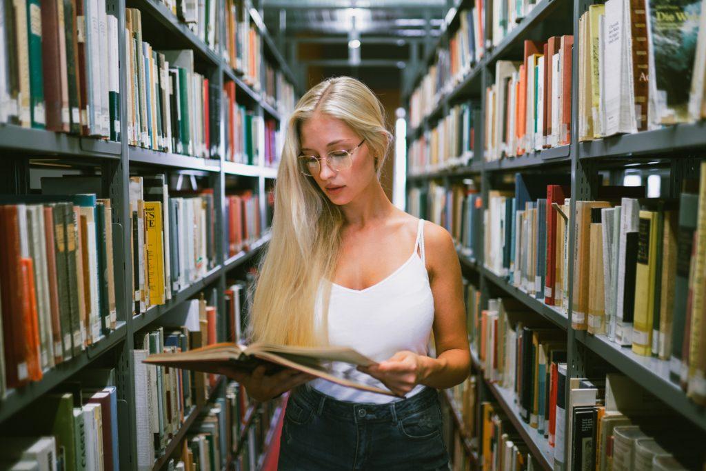 Weibliche Studentin öffnet Buch zwischen Regalen in der Universitätsbibliothek