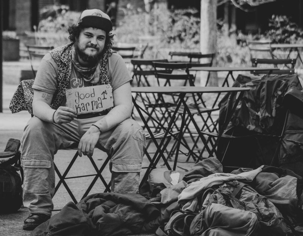 Mann mit Rucksack sitzt auf Stuhl und hält Schild mit gutem Karma günstig zu verkaufen