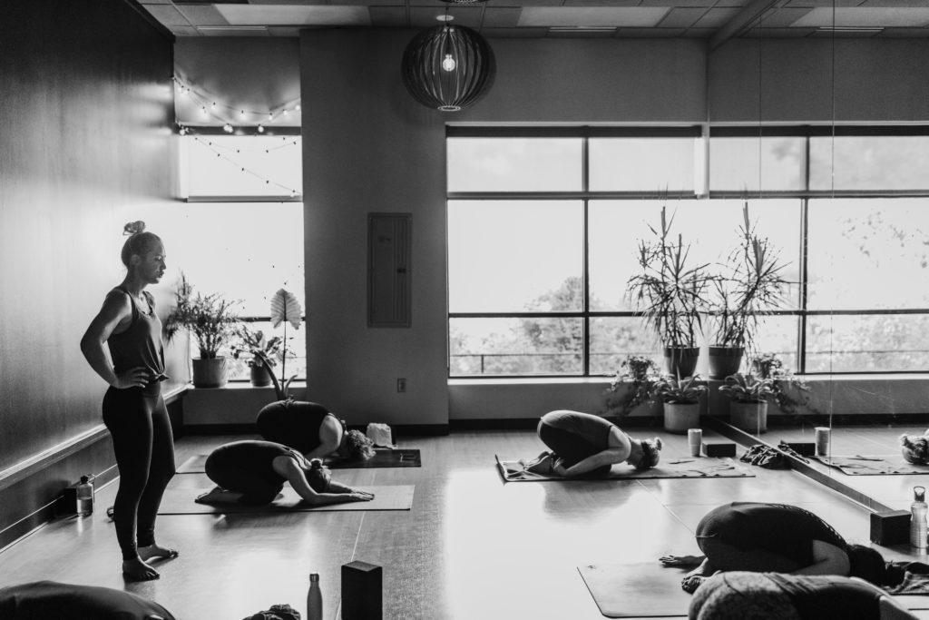 Yogaklasse im Yogastudio mit Schülern in der Stellung des Kindes (Balasana)