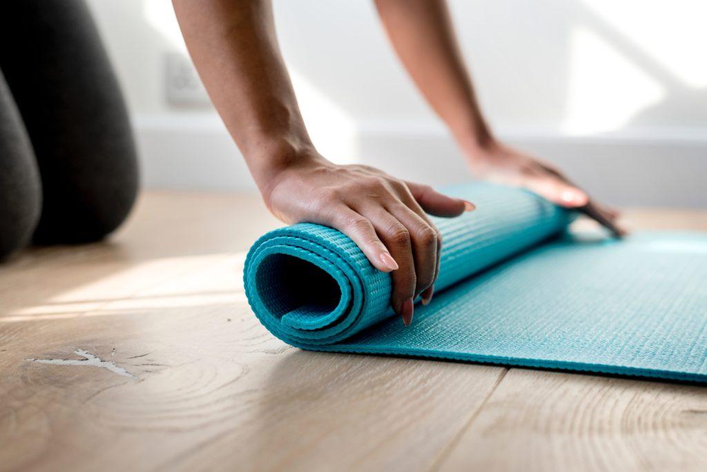 Frau kniet auf Holzboden und entrollt eine türkise Yogamatte aus Gummi