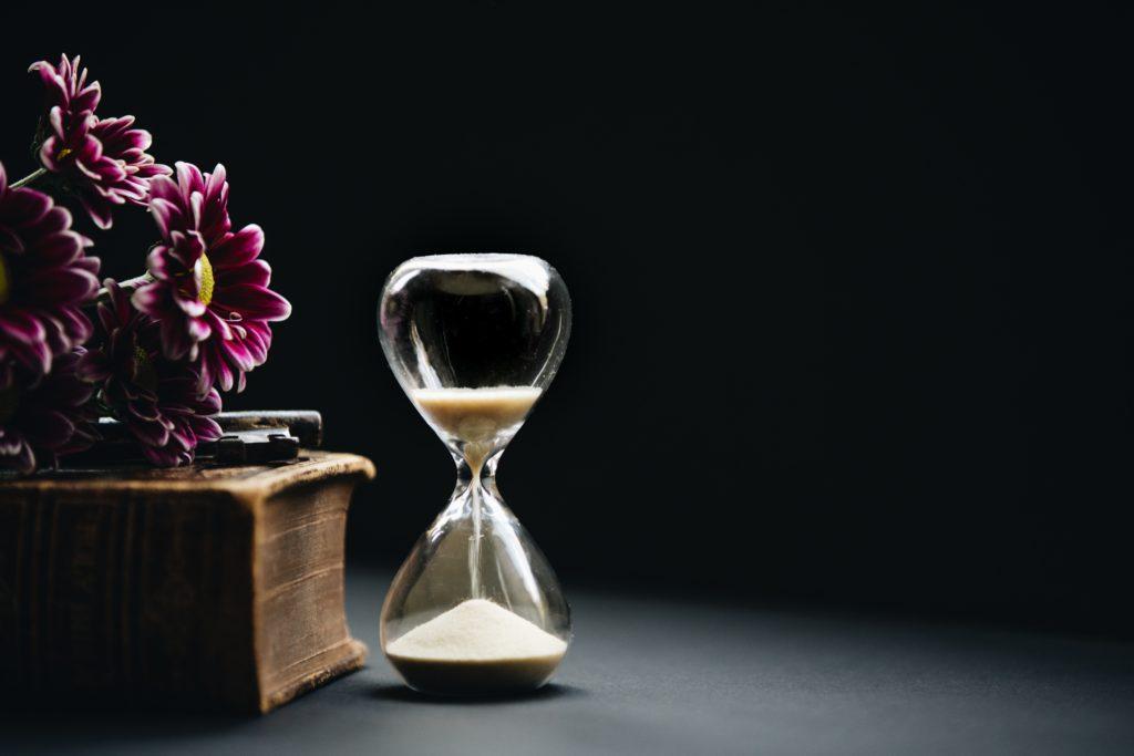 Ablaufende Sanduhr neben Buch auf dem ein Schlüssel und Lila Blumen liegen