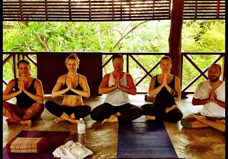 Yogalehrerin Anna Caico mit anderen Yogis sitzend