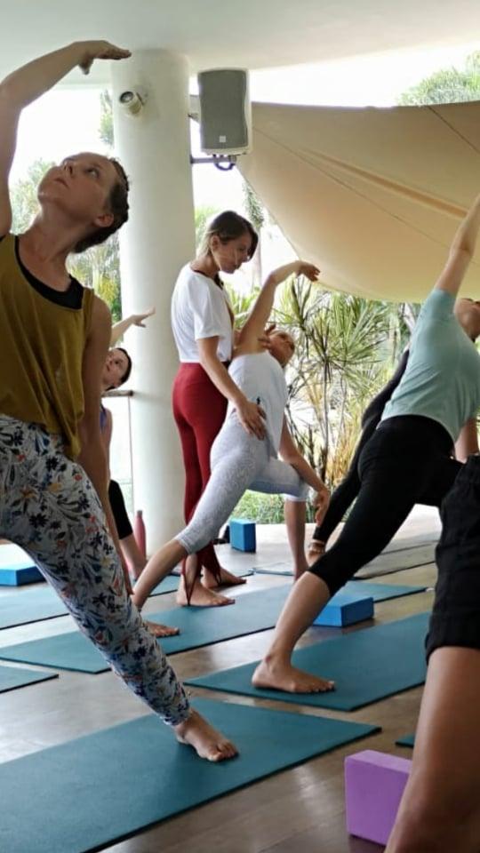Yogalehrerin Dela Marlen korrigiert die Haltung von Yogaschülern