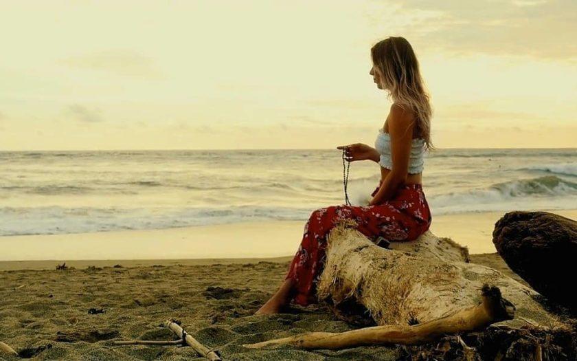 Berliner Yogalehrerin Dela Marlen mit Malakette sitzend am Strand