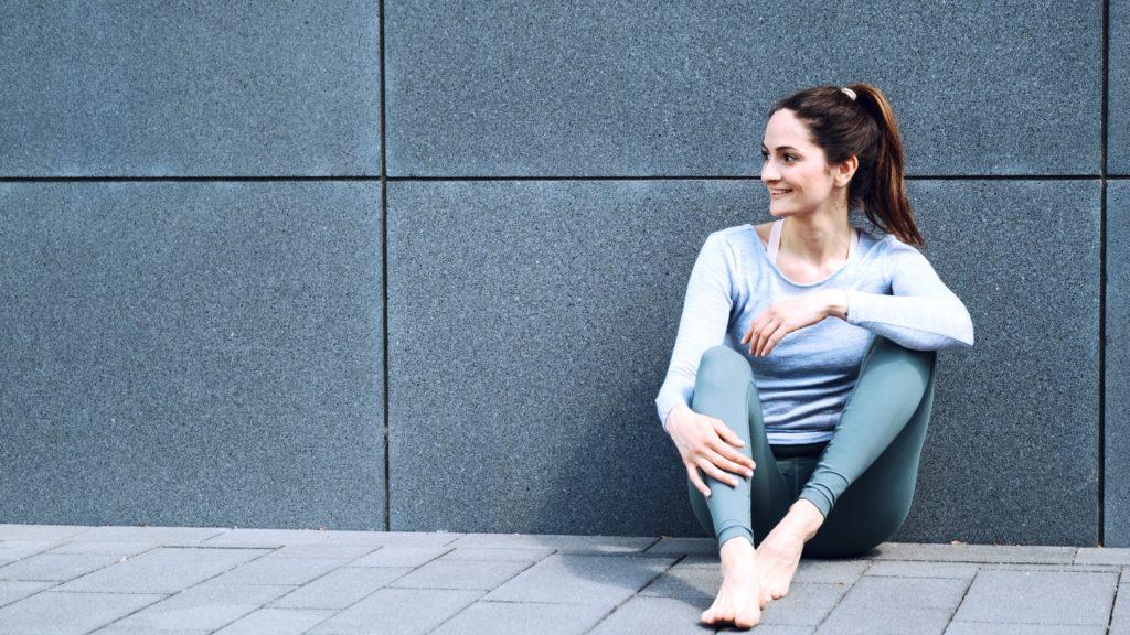 Yoga Lehrerin Jana Seidel sitzt vor einer grauen Wand